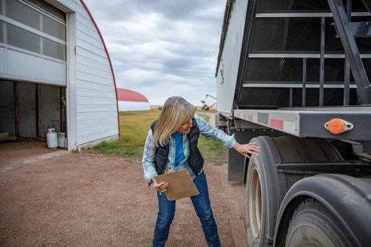 Senior female farmer with clipboard inspecting trailer tires