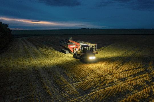 Combine harvester and trailer in rural field at dusk, harvesting crop
