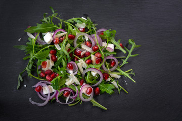 Arugula or rocket salad with pomegranate seeds, red onions and parmesan on a dark slate plate, copy space, high angle view from above