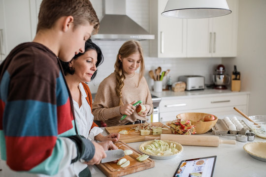 Family preparing apple pie with recipe from digital tablet