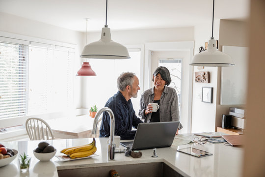 Senior couple planning holiday with laptop and map