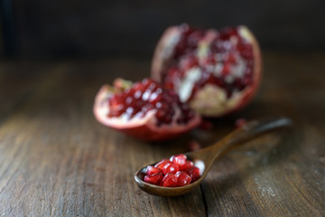 Pomegranate seeds on a spoon and the fruit blurry in the background, dark rustic wooden table with copy space