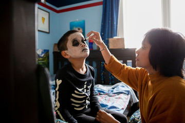 Mother helping son with Halloween makeup