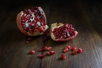 Opened pomegranate fruit with red juicy seeds on rustic wood, dark and moody style, copy space