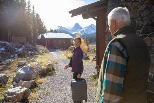 Smiling hotel employee carrying suitcase outside sunny mountain cabin for senior man