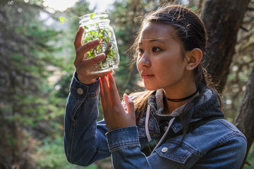 Curious girl collecting insects in jar in woods