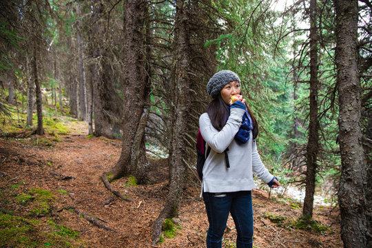 Woman eating apple, hiking in woods