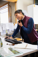 Smiling female hotel receptionist talking on telephone at front desk