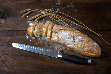 Baguette or French bread half sliced, some wheat ears and a knife on a dark rustic wood, copy space, high angle view from above