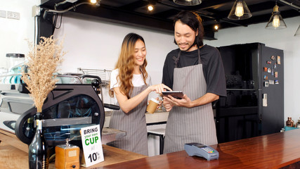 Young asian man and woman barista, small business coffee shop owner holding digital tablet while taking at counter in cafe, business entrepreneur, asia small business concept