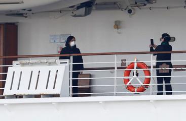 Passengers take photos on a deck of the cruise ship Diamond Princess at Daikoku Pier Cruise Terminal in Yokohama, south of Tokyo, Japan