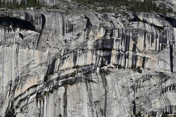 Granite rock formations of Yosemite National Park, California showing vertical water streaks.