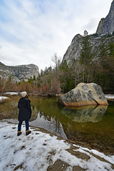 Young woman enjoying view of granite rock formations reflected in Mirror Lake in Yosemite National Park, California.
