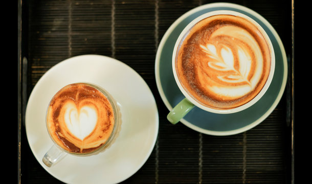 Coffee cups with heart and leaf art on dark tray, top view