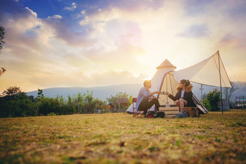 Fototapeten Camping Young couples have good time morning on camping trip with sunrise background. Couples enjoy camping with morning coffee.