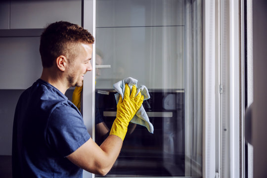 Young bearded smiling positive man with rubber gloves cleaning window with cloth. After rain there is always stains on glass.