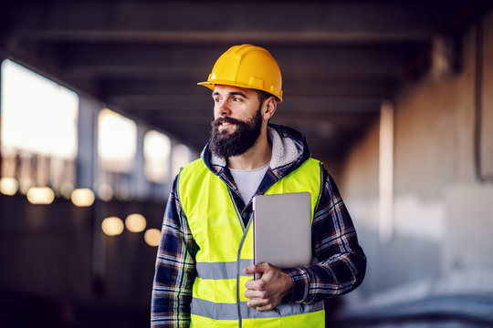 Portrait of highly motivated caucasian hardworking smiling bearded supervisor with helmet on head in vest and with laptop in hands posing on construction site.