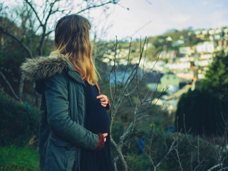 Pregnant woman standing in garden on winter day