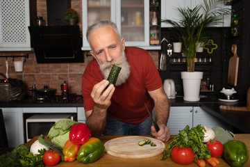 Handsome senior bearded man cooking healthy vegetable salad, cutting cucumber and smiling at camera at home kitchen
