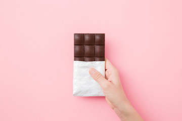 Young woman hand holding chocolate bar on light pink table background. Opened pack. Sweet snack. Close up. Top down view. Papier Peint