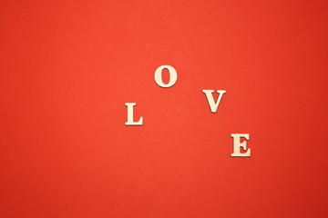 Fototapeta Słowo LOVE ułożone schodkowo, z dewnianych liter, na tle ciepłego czerwonego tła obraz
