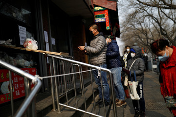 Customers line up outside a store where a ramp is set up to deliver food to customers from the restaurant counter in Beijing