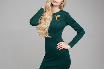 Cropped stock photo of anonymous blonde model with long hair wearing beautiful sking-tight dress of deep green color with golden hummingbird brooch on chest. Holding arms on her hip. Cutout on white