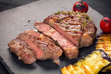 medium rare beef steak on ceramic board with herbs spices and salt.