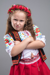 Happy smiling little girl in national Ukrainian folk costume on gray background