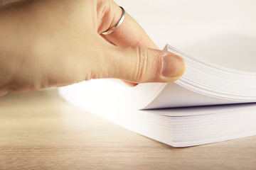 Stack of paper on office desk for report papers . Close up of stack paper. Females hand touching paper, close up view.