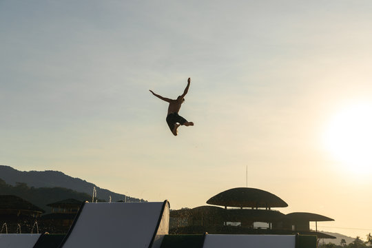Man slide from top to jump up so high at water park with sunset light