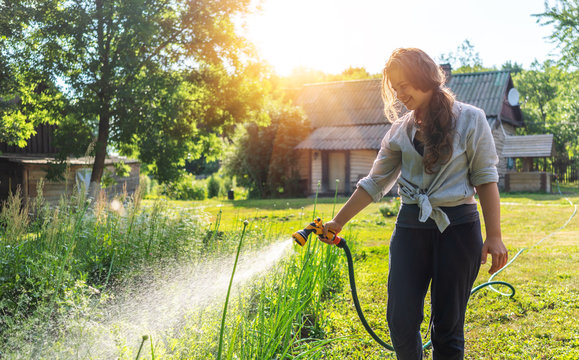 Hipster young woman watering plants a country house, summer and garden care, organic products, eco-friendly lifestyle