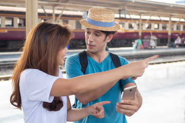 Asian woman speaking fluent foreign language with foreigner; concept of communication with foreign...