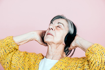 grey hair senior woman listen to the music with headphones and closed eyes - modern cool hipster relax lifestyle concept