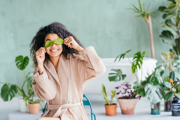 Stores à enrouleur Detente Smiling brunette woman in a towel on the head with white nourishing mask or creme on face and green leaf in hand on white background isolated. Skincare cleansing eco organic