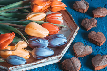 retro style picture on the table are hearts of wood, and on a tray are tulips