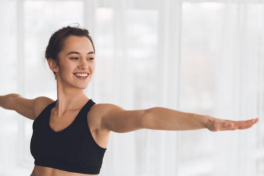 Woman exercising yoga in warrior pose in modern studio