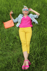 A young woman with a bag is on the background of green grass in yellow pants and a pink jacket with sandals.Urban summer style.