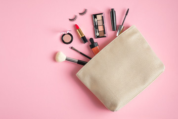 Makeup bag with cosmetic products spilling out on to pastel pink background. Flat lay, view from above. Stylish make up artist pouch with beauty products