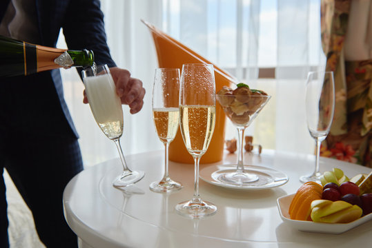 Man in suit pouring champagne from bottle into glass indoors, copy space. Champagne party. Wedding reception
