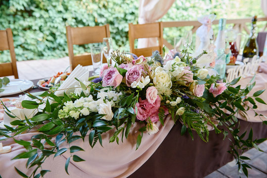 Lush floral arrangement on wedding table outdoors. Wedding presidium in restaurant, copy space. Banquet table for newlyweds with pink and purple rose flowers. Luxury wedding decorations
