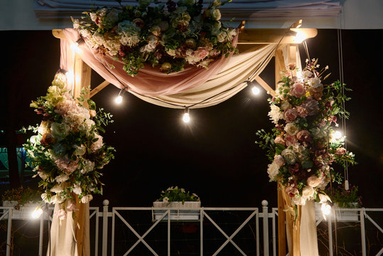 Night wedding ceremony with arch, flowers, cloth and bulb lights on the backyard outdoors, copy space. Wedding decor