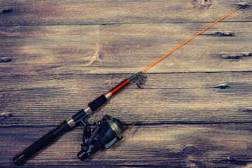 Fishing spinning lies on a wooden background