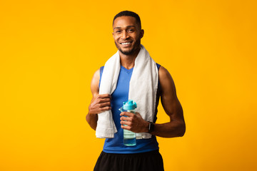 Healthy afro guy holding bottle of water