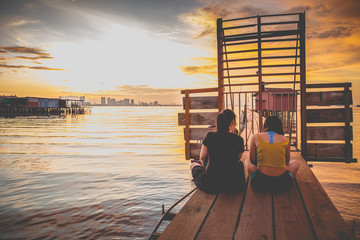 Two tourist woman on wooden bridge watching sunrise at Chew jetty.