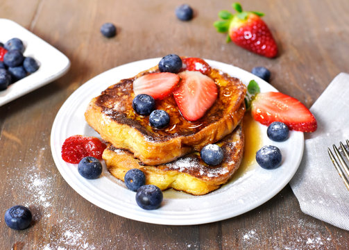 Delicious french toast with fresh fruits and maple sirup. Tasty breakfast scene or dessert with toast, strawberries, blueberries and powdered sugar.