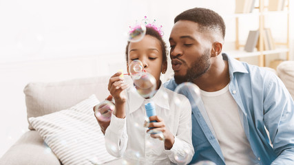 Handsome man spending time with daughter, blowing soap bubbles together