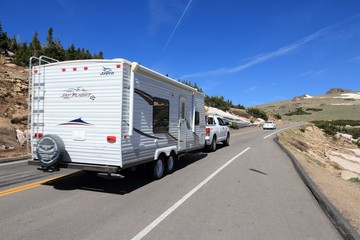 ROCKY MOUNTAINS, USA - JUNE 19, 2013: People drive with camping trailer along Trail Ridge Road in Rocky Mountain National Park, Colorado. RNMP has 3,176,941 annual visitors (2011).