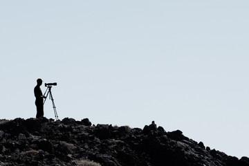 Fotograf mit Kamera und Teleobjektiv auf Stativ