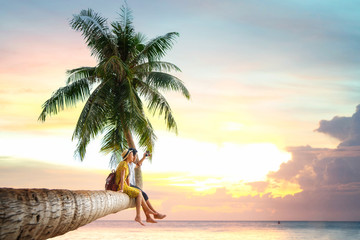 Wall Mural - Asian couple sit on coconut tree